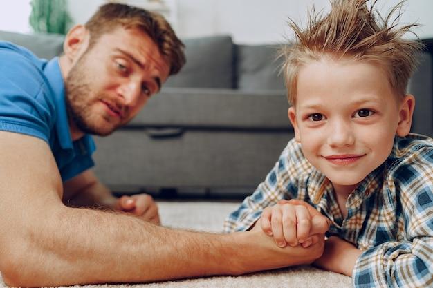 Padre e figlio braccio di ferro sul tappeto a casa clsoe
