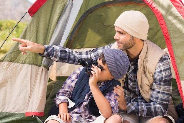 Padre e figlio accanto alla loro tenda in campagna Foto Premium