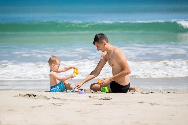 Padre e figlio costruiscono un castello di sabbia sulla spiaggia