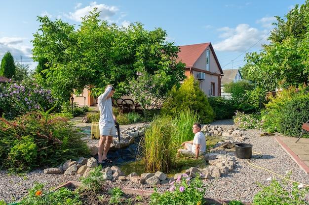 Padre e figlio che puliscono il fondo del laghetto da giardino con un'idropulitrice dal fango