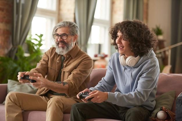 Padre e figlio in competizione tra loro giocando al videogioco sul divano della stanza