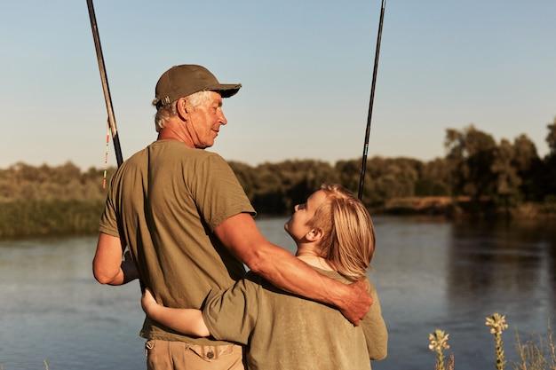 Padre e figlio vanno a pescare, in piedi vicino al lago e abbracciati, guardandosi l'un l'altro, indossando abiti verdi, la famiglia trascorrendo del tempo insieme all'aria aperta e godendo della splendida natura.