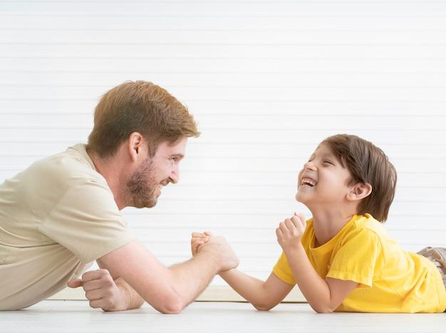 Padre e figlio che hanno una competizione di braccio di ferro a casa.