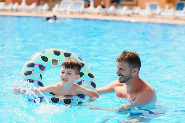 Padre e figlio che hanno divertimento in piscina.