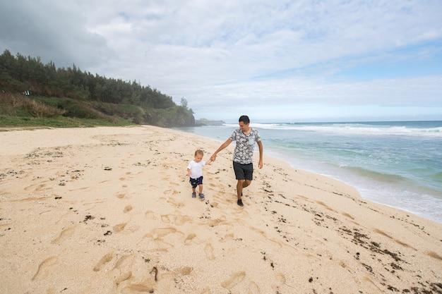 Padre e figlio che si tengono per mano camminano insieme sulla spiaggia