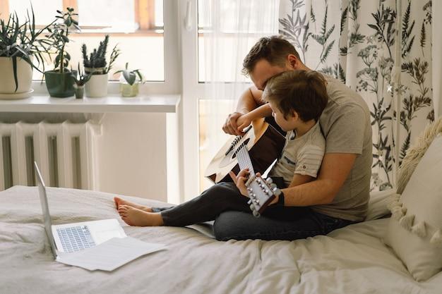 Padre e figlio imparano a suonare la chitarra acustica in una lezione online