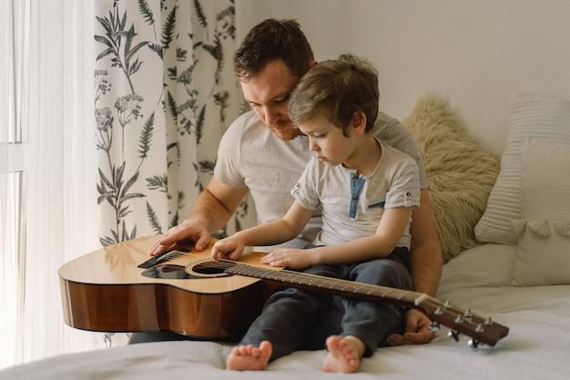 Padre e figlio che imparano a suonare la chitarra acustica