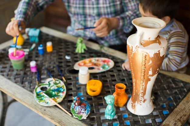 Padre e figlio dipingono un vaso