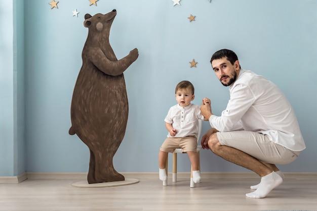 Padre e figlio giocano vicino a un grande orso di legno nella stanza dei bambini
