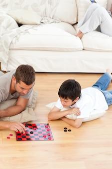 Padre e figlio che giocano insieme a dama sdraiato sul pavimento