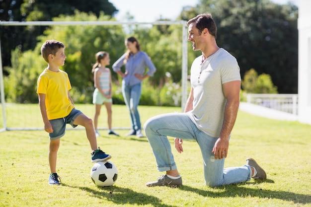 Padre e figlio che giocano a calcio nel parco