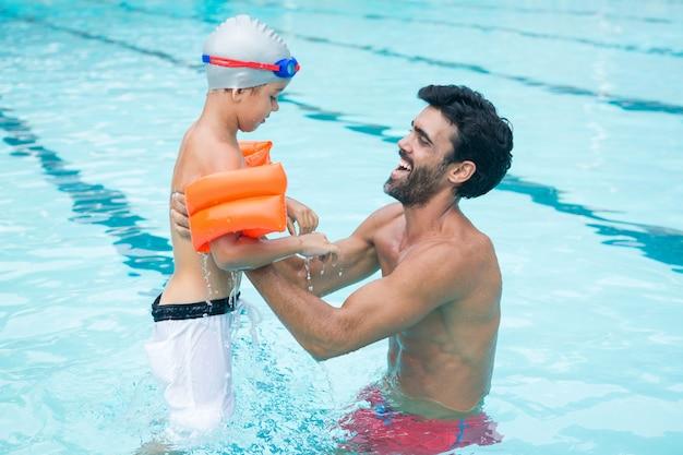 Padre e figlio che giocano in piscina