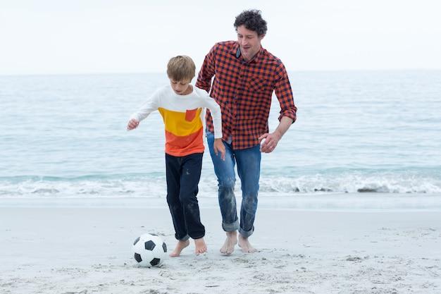 Padre e figlio che giocano a calcio in spiaggia
