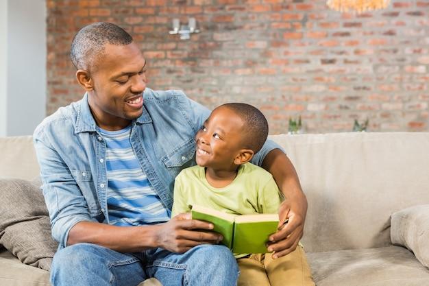 Padre e figlio leggendo sul divano