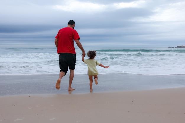 Padre e figlio che corrono sulla spiaggia estiva. papà e bambino si divertono all'aperto.