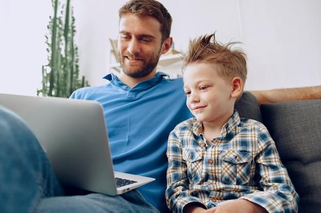 Padre e figlio seduti sul divano e guardare qualcosa sul computer portatile