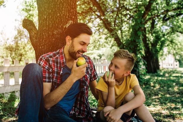 Padre e figlio seduti insieme sotto l'albero e mangiando mela