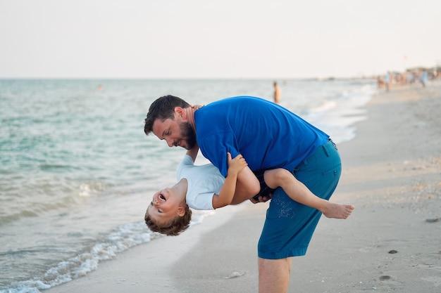 Padre figlio trascorrere del tempo insieme vacanza al mare giovane papà bambino piccolo ragazzo che cammina spiaggia
