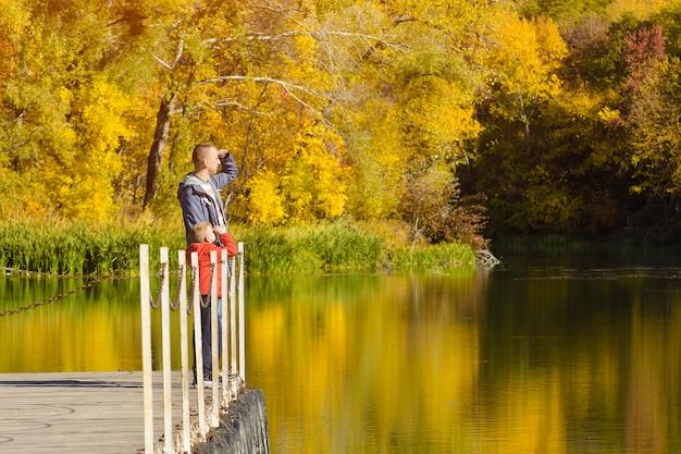 Padre e figlio stanno sul molo vicino al fiume. giornata di sole autunnale