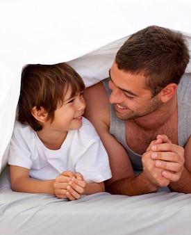 Padre e figlio che parlano sotto le lenzuola