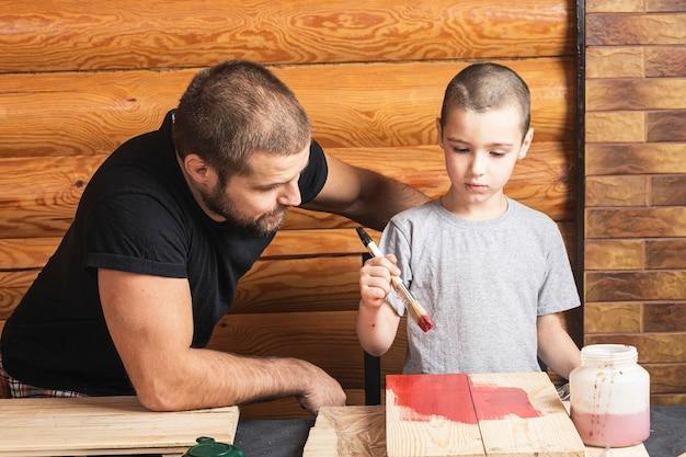 Padre e figlio insieme fanno una casetta per uccelli in legno in officina