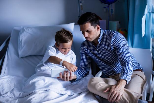 Padre e figlio che per mezzo della compressa digitale