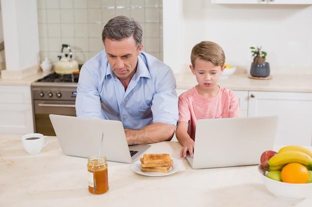 Padre e figlio che utilizza computer portatile nella cucina