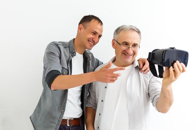 Padre e figlio in occhiali virtuali, muro bianco isolato.