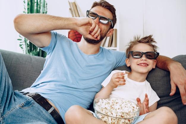 Padre e figlio che guardano film a casa con gli occhiali 3d e mangiano popcorn