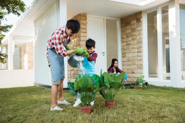 Padre e figlio che innaffiano insieme una pianta davanti alla loro casa