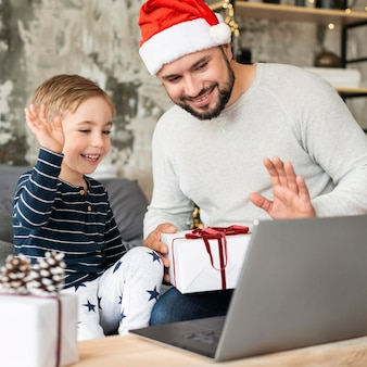 Padre e figlio che salutano i parenti in videochiamata il giorno di natale