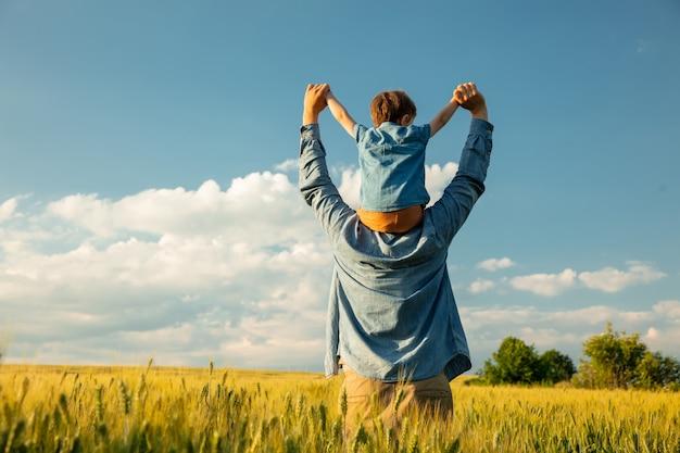 Padre e figlio nel campo di grano, figlio seduto sulle spalle di suo padre