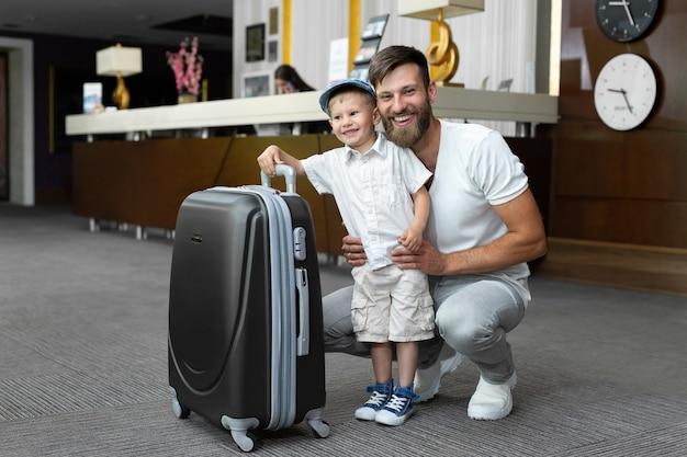 Padre e figlio con una valigia alla reception dell'hotel.