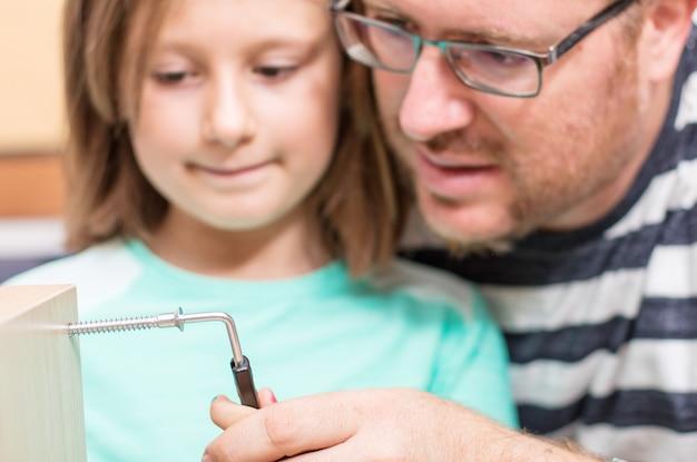 Padre e figli stanno costruendo i mobili in casa