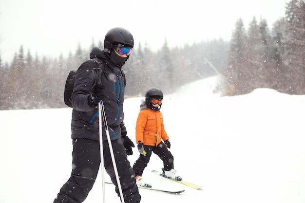 Il padre insegna al figlio a sciare su una pista innevata