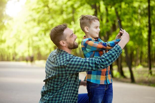 Un padre insegna a suo figlio a farsi un selfie con il telefono in un parco in una soleggiata giornata estiva