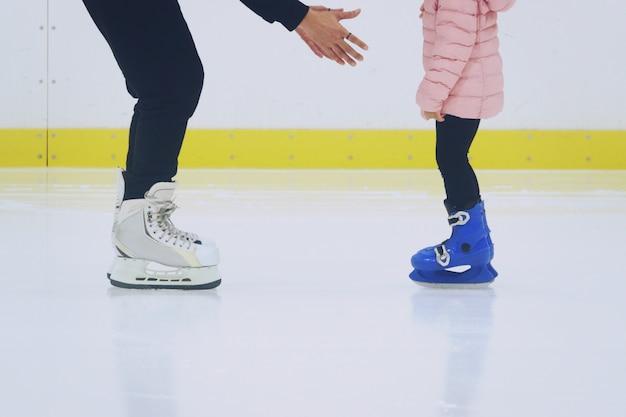Padre che insegna alla figlia a pattinare sulla pista di pattinaggio sul ghiaccio