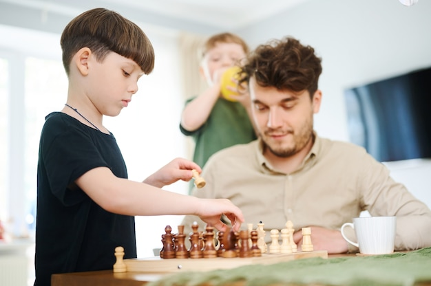 Padre che insegna al figlio a giocare a scacchi concetto di educazione e insegnamento