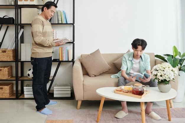 Padre e figlio adolescente leggono libri e bevono tè con snack quando rimangono a casa a causa della pandemia di covid-19