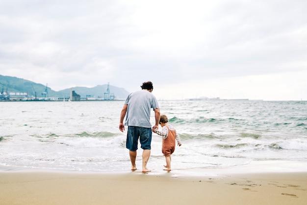 Padre e figlio di tre anni si godono un pomeriggio nuvoloso in spiaggia durante il fine settimana