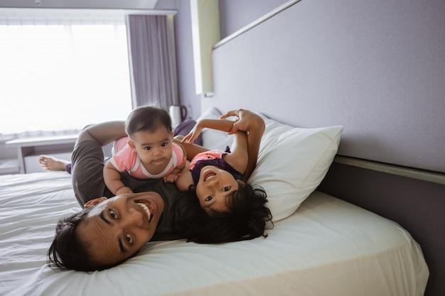 Padre e i due figli giacciono sul letto