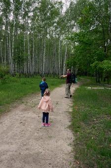 Padre e due figli, figlio e figlia che fanno un'escursione nella foresta. passeggiata in famiglia. l'ora legale insieme in campeggio. buona festa del papà.