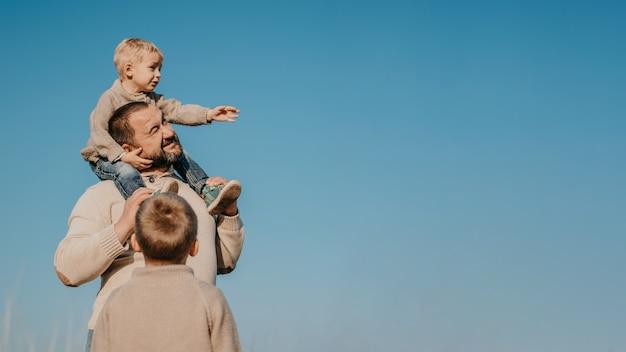 Padre e due figli che giocano, si divertono