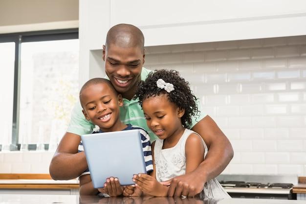 Generi facendo uso della compressa con i suoi bambini in cucina