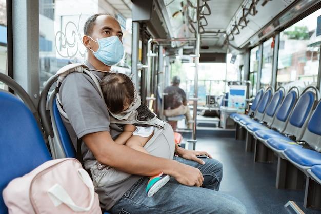 Un padre che indossa una maschera siede su una panchina con in braccio una piccola bambina che dorme sull'autobus lungo la strada