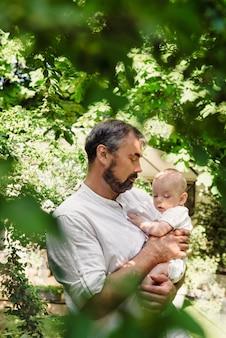Padre con il neonato in foglie verdi che riempiono bello e tenero, la paternità. piccolo figlio carino sulle ginocchia di papà