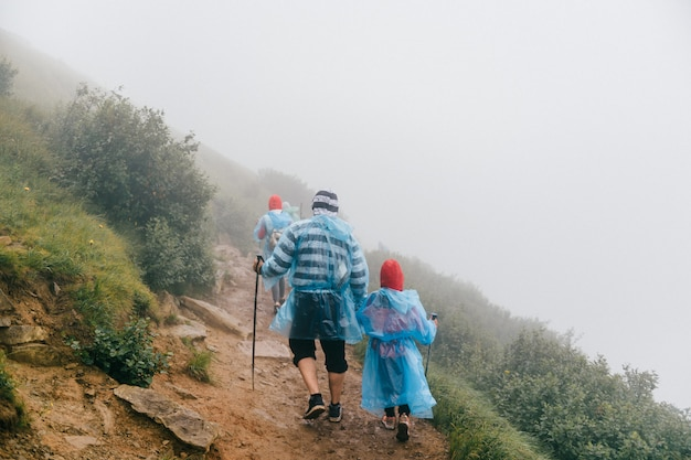 Padre con bambino, escursioni in montagne nebbiose. trekking in montagna. famiglia in viaggio.