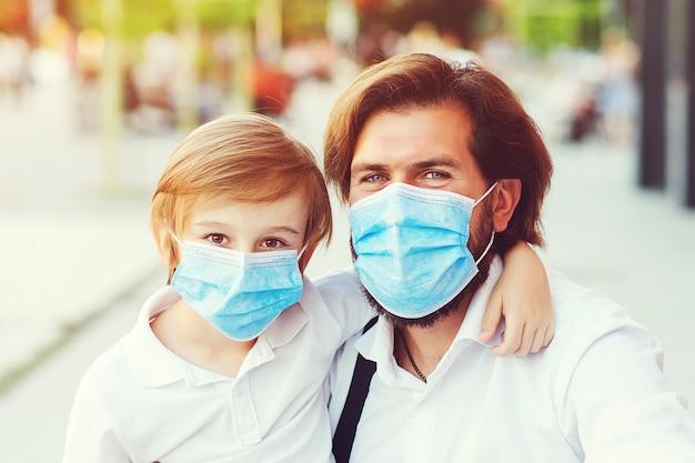 Padre con bambino in mascherina medica in città.