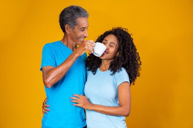 Padre con una tazza di caffè che passa vicino al naso di sua figlia per farle annusare l'aroma. foto per le campagne del caffè e per la festa del papà