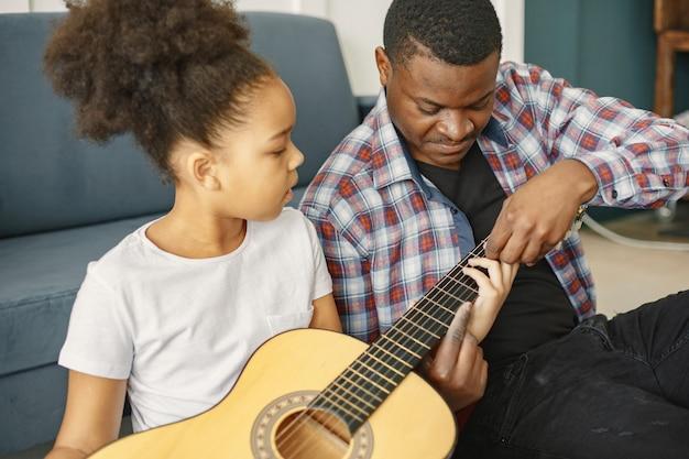 Padre con figlia sul divano. ragazza che tiene una chitarra. imparare la chitarra.